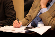 Executive writing. On paper during a conference with translation Royalty Free Stock Image