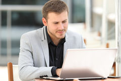 Executive writing on line in a laptop in a bar Royalty Free Stock Photo