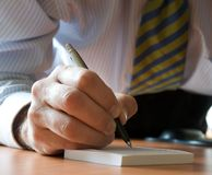 Executive writing a note. Closeup of a hand writing a note Royalty Free Stock Photos