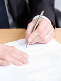 Executive writing in the writing pad. Sitting at the table business man making notes in the writing pad Stock Images