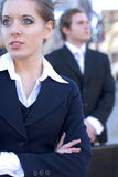 Executives. A young female executive stands in the foreground gazing in one direction, while a male executive stands in the background looking in the other stock photo