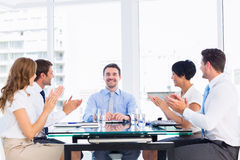 Executives clapping around conference table. Business executives clapping around conference table in a bright office stock image