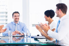 Executives clapping around conference table Stock Images