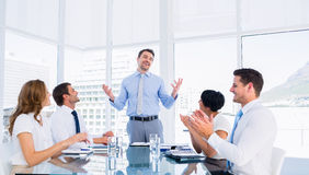 Executives clapping around conference table. Business executives clapping around conference table in a bright office royalty free stock photography