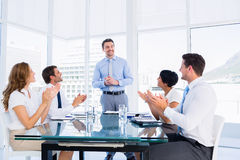 Executives clapping around conference table. Business executives clapping around conference table in a bright office royalty free stock image