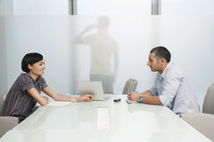 Executives At Conference Table With Man On Call Across Transluce Stock Photo