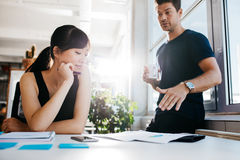 Executives discussing new business ideas in office. Two young executives discussing new business ideas in office. Colleagues working together on paperwork royalty free stock photos