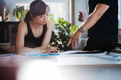 Executives discussing new business ideas in office. Two young executives discussing new business ideas in office. Colleagues working together on paperwork. Woman stock photography