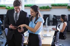 Executives discussing over tablet in background other executive working. At office royalty free stock photography