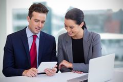 Composite image of executives discussing over tablet while sitting against white background royalty free stock photo