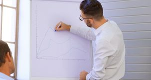 Executives discussing over whiteboard in conference room 4k stock footage
