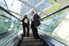 Executives on an Escalator. A young male and female executive ride an escalator together in a modern hi-tech city setting royalty free stock photos