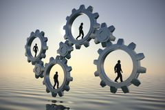 Executives in Gears of teamwork at sea at sunrise over  water. Executives walking inside gears at sea at dawn demonstrate the power of cooperation and synergy Royalty Free Stock Image