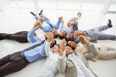 Executives holding hands together in circle. High angle view of happy executives holding hands together in circle stock image