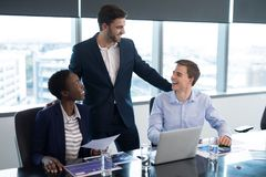 Executives interacting with each other. In boardroom Stock Photos