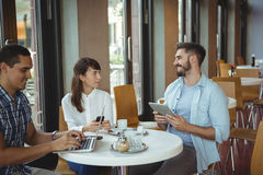 Executives interacting while using, mobile phone, digital tablet and laptop Stock Images