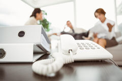 Executives with land line phone and folders in foreground Stock Photos