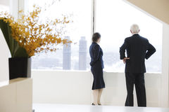 Executives looking out of office window. Stock Photos