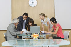 Executives In Meeting At Office. Businesspeople having meeting with laptop in conference room stock image