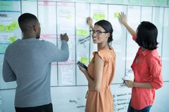 Executives preparing sticky notes on whiteboard. In office stock photos