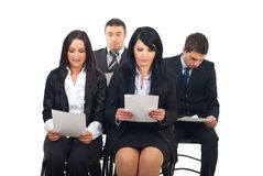 Executives reading at conference. Four executives people sitting on chairs at conference and reading their paperwork isolated on white background stock image