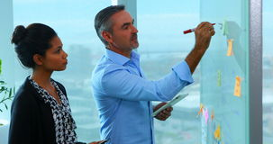 Executives reading sticky notes on glass board. In office stock video
