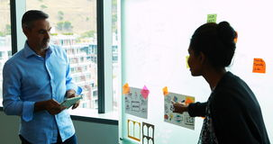 Executives reading sticky notes on glass board. In office stock footage