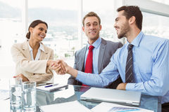 Executives shaking hands in board room meeting Royalty Free Stock Image