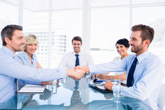 Executives shaking hands during business meeting. At office desk stock photo