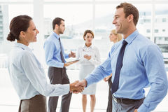 Executives shaking hands with colleagues behind. In office royalty free stock photo