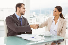 Executives shaking hands in office Stock Image