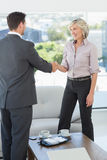 Executives shaking hands over a coffee table at home Royalty Free Stock Photo