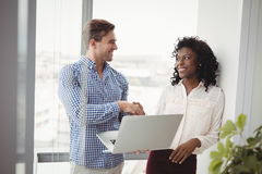 Executives shaking hands while using laptop Royalty Free Stock Photos
