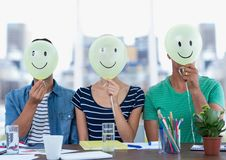 Executives sitting at desk with smiley faces on their face. Digital composition of executives sitting at desk with smiley faces on their face royalty free stock image