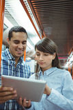 Executives using digital tablet travelling in train Royalty Free Stock Image