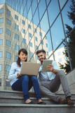 Executives using laptop and digital tablet outside office building Royalty Free Stock Photo