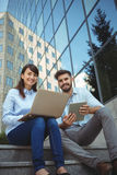 Executives using laptop and digital tablet outside office building Royalty Free Stock Image