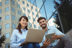 Executives using laptop and digital tablet outside office building Stock Images