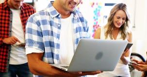 Executives using laptop, mobile phone, digital tablet in office. Smiling executives using laptop, mobile phone, digital tablet in office stock footage