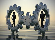 Executives walking inside gears at sea since dawn. Two executives walking inside gears at sea at dawn demonstrates their talent and effectiveness Royalty Free Stock Photo