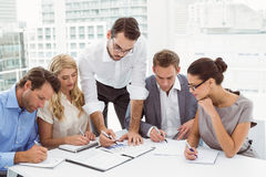 Executives writing notes in office. Young business people writing notes in office stock photography