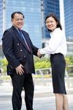 Executivo asiático fêmea novo e homem de negócios asiático superior que agitam as mãos Fotos de Stock