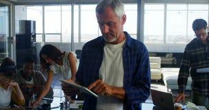 Executivo atento que usa a tabuleta digital video estoque