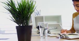 Executivo com auriculares que escreve no diário na mesa no escritório 4k video estoque