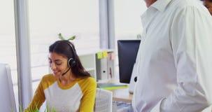 Executivo com auriculares usando computadores na mesa no escritório 4k video estoque