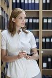 Executivo com parte superior da palma na sala de armazenamento do arquivo Fotografia de Stock