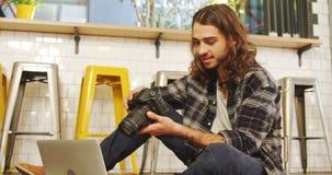 Executivo criativo que revê as fotos em sua câmara digital 4K 4k video estoque