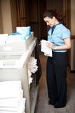 Executivo das tarefas domésticas que dobra a toalha de mão Imagens de Stock Royalty Free