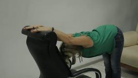 Executivo de mulher que faz esticando o exercício em sua poltrona no local de trabalho Movimento lento video estoque