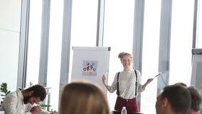Executivo de propaganda fêmea que usa a plataforma do fã da cor ao dar a apresentação vídeos de arquivo